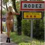 Elisa nua diante da placa de entrada da cidade de Rodez